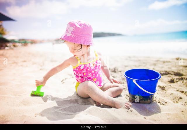 Baby spielt am Sandstrand mit Eimer und Spaten Stockbild