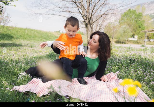 Mutter und Sohn auf einer Decke in der Natur Stockbild