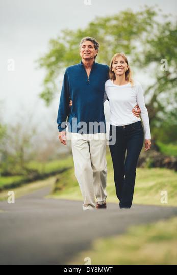 Happy mittleren gealterten Liebespaar zu Fuß auf wunderschönen Country road Stockbild