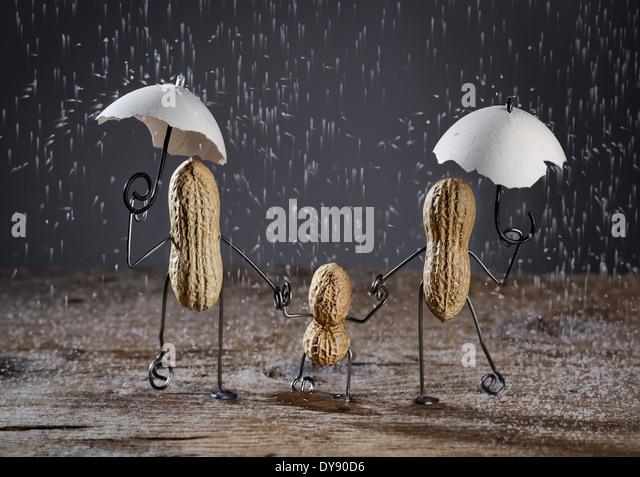 Drei Gebäude der Familie mit einem Kind in der Regen machte der Salzkörner Erdnüsse Stockbild
