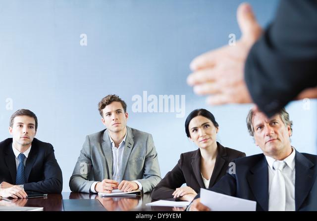 Geschäftspartnern hören, wie Kollege Präsentation während der Sitzung macht Stockbild