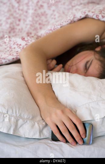 Frau schläft im Bett mit Smartphone in der hand Stockbild