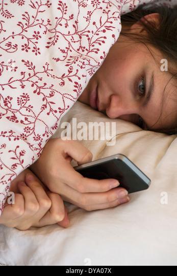 Frau liegend Bett Smartphone mit unglücklichen Gesichtsausdruck betrachten Stockbild