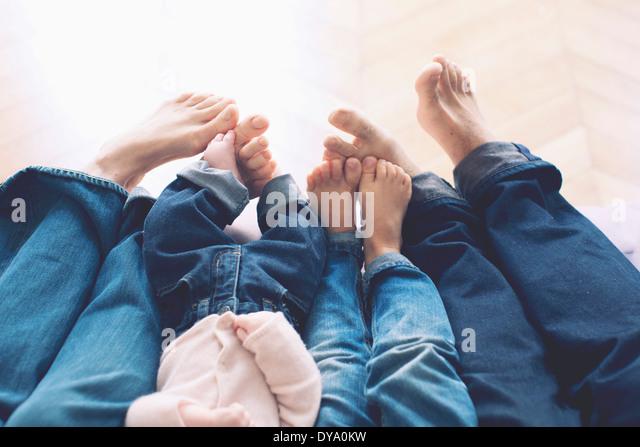 Ausgestreckten Beinen und barfuss Familie mit zwei Kindern Stockbild