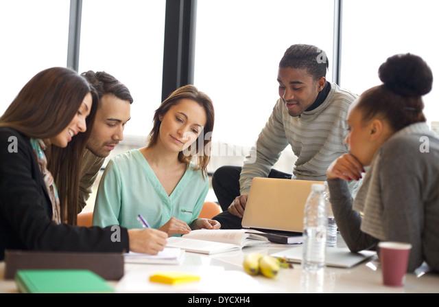 Heterogene Gruppe von jungen Studenten gemeinsam an Schulaufgaben. Multiethnische Leute studieren zusammen an einem Stockbild