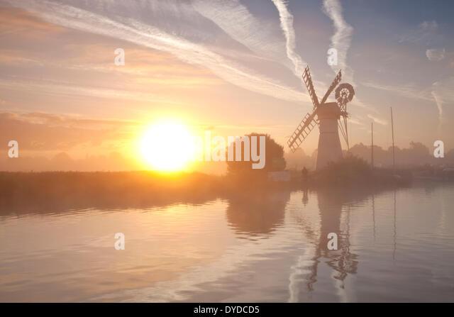 Thurne Mill bei Sonnenaufgang an einem nebligen Morgen auf den Norfolk Broads. Stockbild