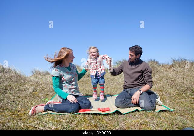 Eine junge Familie, die Spaß auf den Sanddünen am Horsey Strand an der Küste von Norfolk. Stockbild