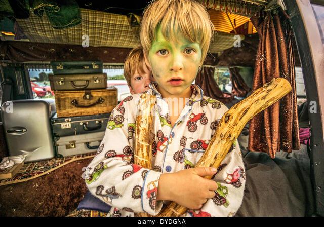 Zwei Jungs, die Spaß in einem VW-Wohnmobil auf einem Festival. Stockbild