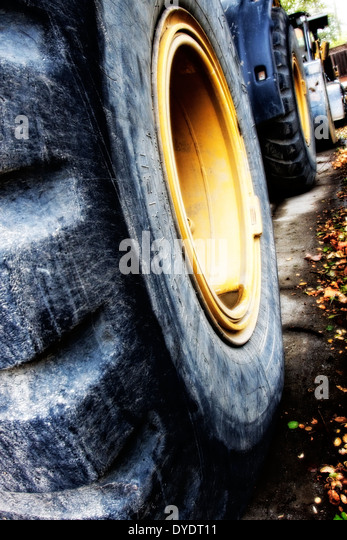 Die stilisierte Abbildung des riesigen Planierraupe Reifen aufgereiht entlang einer Straße bei Bauvorhaben Stockbild