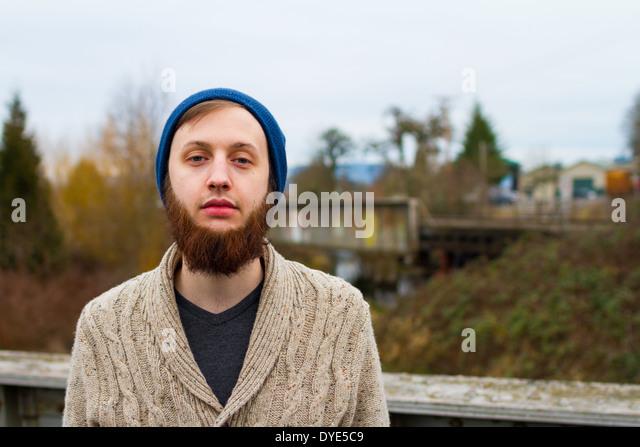 Hipster-Kerl, der moderne Herrenmode in diesem trendigen Porträt zeigt. Stockbild