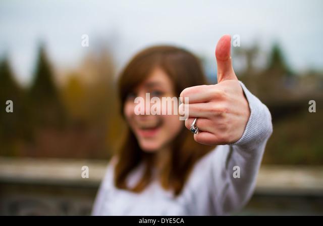 Schöne Mädchen ein Daumen hoch Zeichen mit ihrer Hand und den Fingern für dieses einmalige Genehmigung Stockbild
