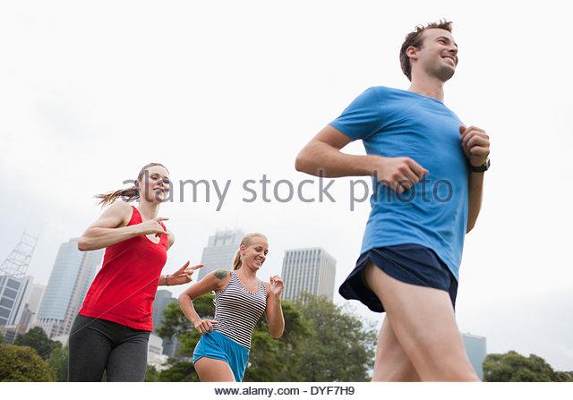 Freunde im Stadtpark laufen Stockbild