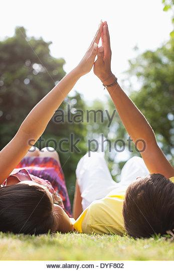 Jugendliche, die Verlegung in Rasen, Hand in Hand Stockbild
