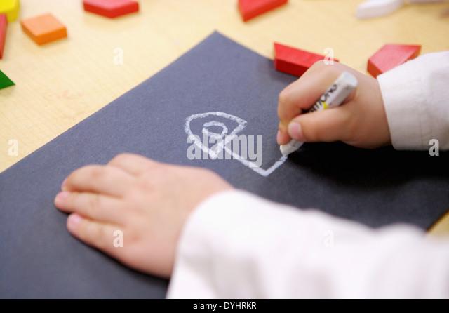 Junge Kinder Zeichnung mit Kreide auf schwarzem Papier Stockbild