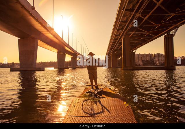 Ein Mann Angeln neben zwei Brücken in innen Sydney, Australien Stockbild