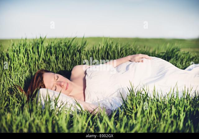 Junge Frau schlafen auf weiches Kissen frischen Frühling Gras Stockbild