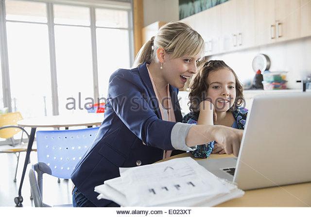 Schulmädchen und Lehrer mit Laptop im Klassenzimmer Stockbild
