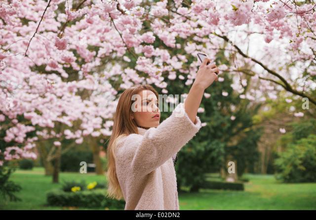 Kaukasische Mädchen malte Blüte Blumen mit ihrem Handy. Attraktive Frau fotografieren Blumen im Frühlingspark Stockbild