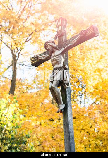 Jesus Christus am Kreuz mit Herbst Bäume im Hintergrund. Friedhof in Stockholm, Schweden. Stockbild