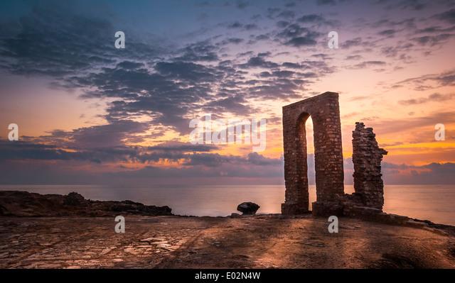 Sonnenuntergang über dem Meer und felsigen Küste mit antiken Ruinen und Tor nach Afrika in Mahdia, Tunesien Stockbild