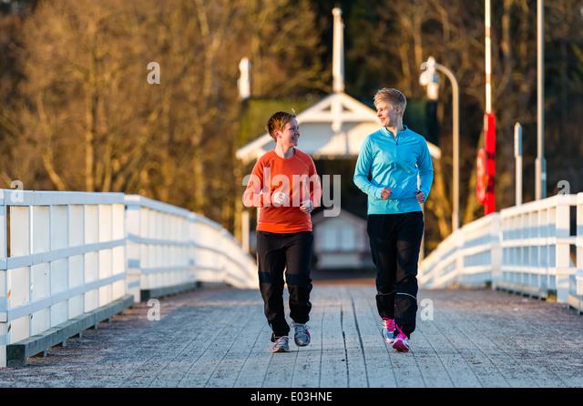 Zwei Frauen zusammen Joggen entlang der Brücke bei Sonnenaufgang Stockbild