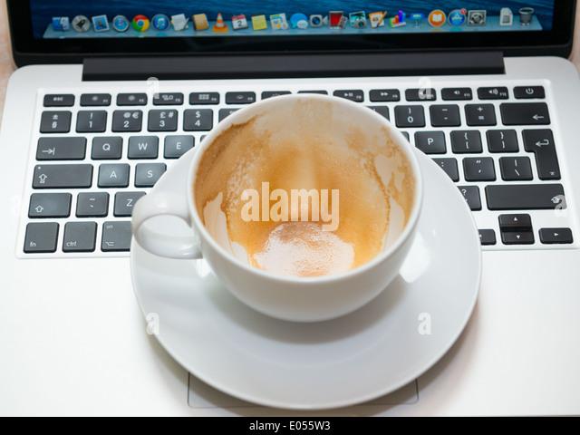 Eine leere Cappuccino-Tasse und Untertasse auf einem laptop Stockbild