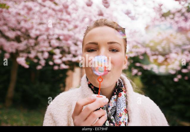 Porträt der schönen jungen Frau bläst Seifenblasen im Park. Hübschen weiblichen Modell mit Blase Stockbild