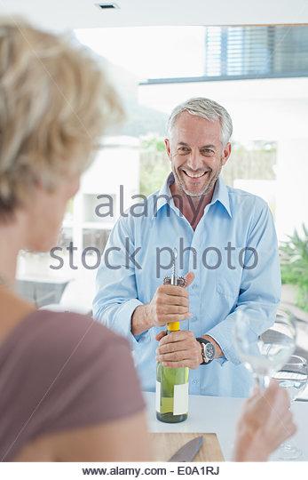 Mann Eröffnung Wein für Frau Stockbild