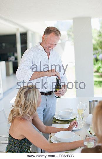 Öffnen der Weinflasche für Frau Mann Stockbild