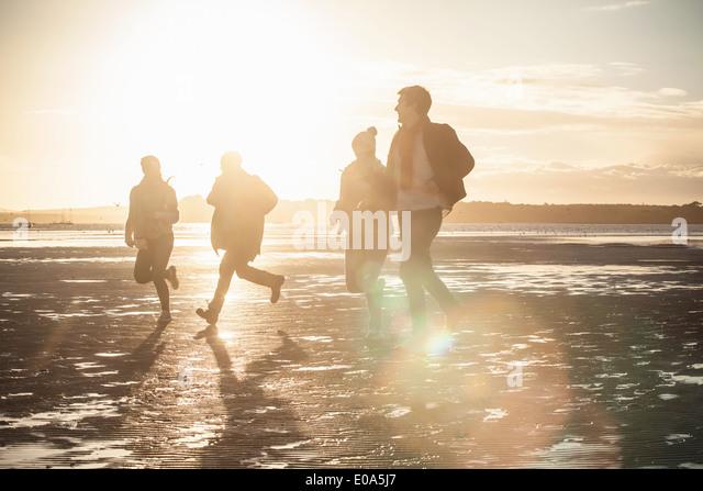 Erwachsene Freunde Rennen einander am Strand Stockbild