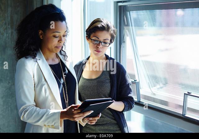 Zwei Geschäftsfrauen Blick auf digital-Tablette im Büro Stockbild
