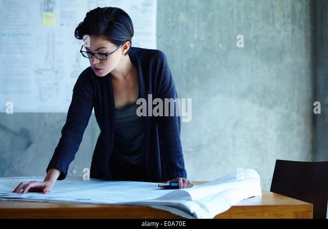 Geschäftsfrau, Studium der Baupläne im Büro Stockbild