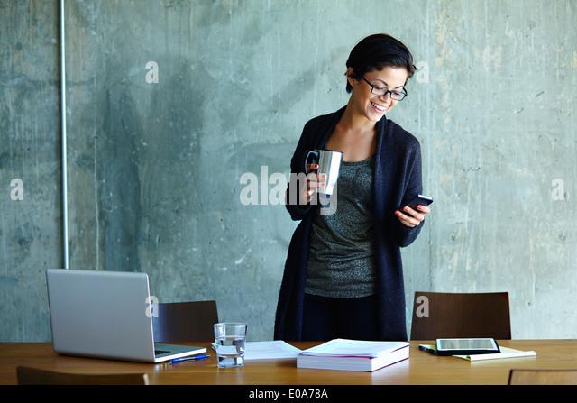 Junge Geschäftsfrau Blick auf Smartphone im Büro Stockbild
