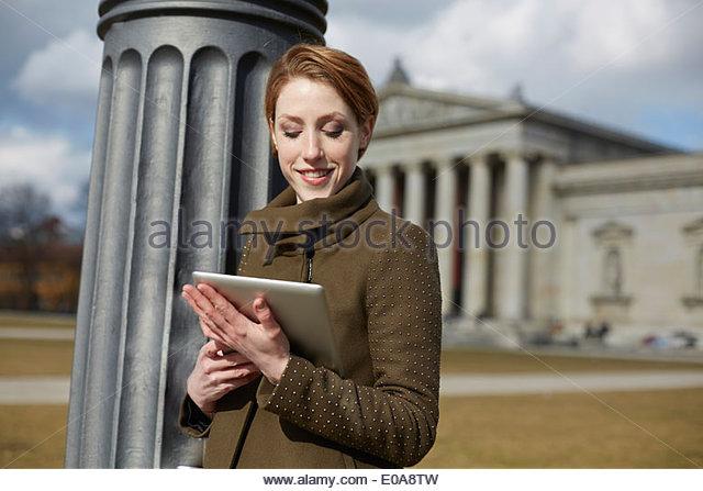 Frau mit digital-Tablette, Denkmal im Hintergrund, München, Deutschland Stockbild
