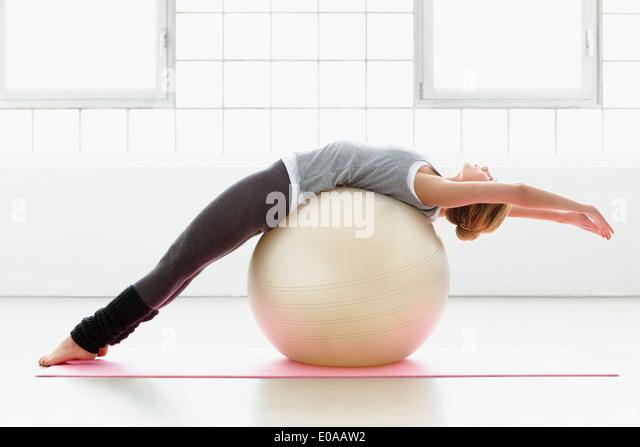 Junge Frau stretching auf Gymnastikball Stockbild