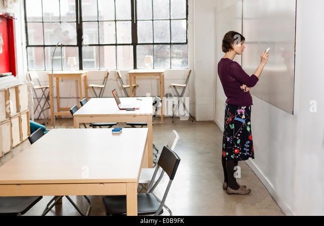 Junge weibliche Designer-Zeichnung auf Whiteboard im Designstudio Stockbild