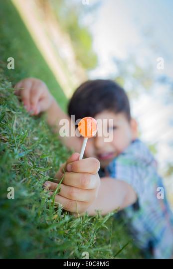 Hübscher Junge seine Lollipop im Freien auf dem Rasen genießen. Stockbild