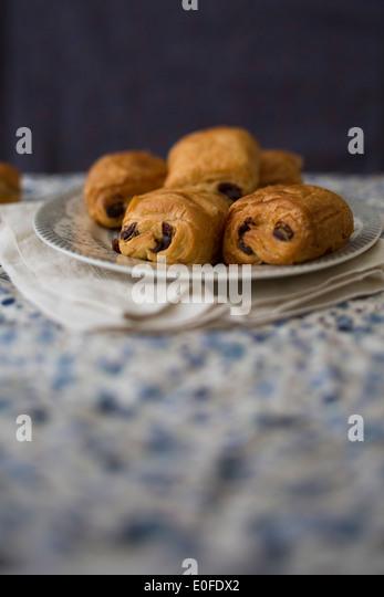 Teller mit Pain Au Chocolat auf einem blau floral Tischdecke und dunkelblauen Hintergrund Stockbild