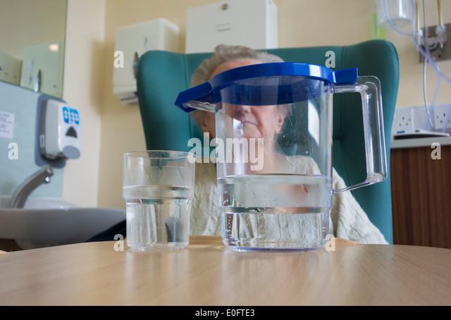 Ältere Dame in ihre neunziger Jahre Vorsitz im NHS Krankenhaus mit Krug Wasser am Tisch sitzen. Stockbild
