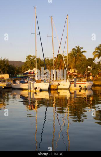 Segelboote angedockt an einen Yachtclub reflektieren in ruhigem Wasser bei Sonnenuntergang. Stockbild