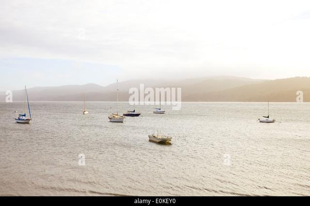 Eine Gruppe von Segelboote auf dem Wasser in den Nachmittag Licht verankert. Stockbild