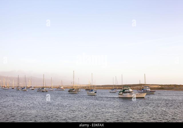 Eine Gruppe von Segelboote auf dem Wasser im Abendlicht verankert. Stockbild