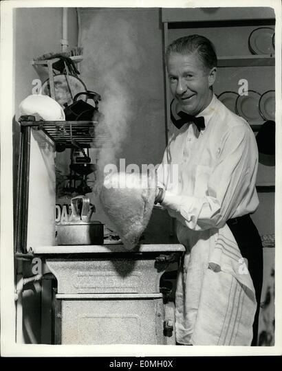 7. Juli 1955 - Aage Thaarup die Modistin produziert seine neuesten Styles über die Küche Spüle: Aage Stockbild