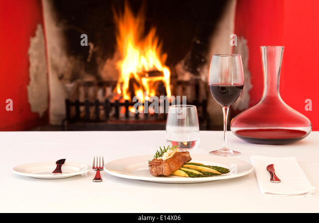Gehobene Küche, Sirloin Steak, Wein Glas, vor einem offenen Kamin Stockbild