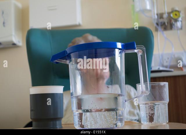 Ältere Dame in ihre neunziger Jahre im Stuhl auf Krankenstation mit Krug Wasser am Tisch sitzen. Stockbild