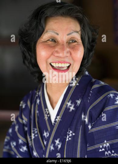 Schöne ältere Okinawan Frau tragen Yukuata und Lächeln auf den Lippen. Ryukyu Mura, Okinawa, Japan Stockbild