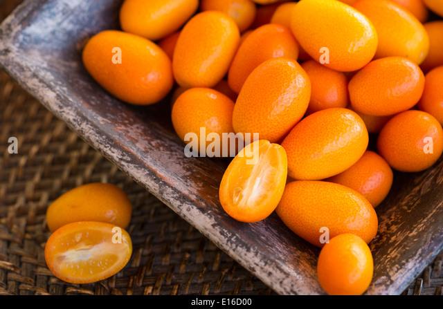 Kumquats in quadratischen Keramikschale auf gewebte rustikale Tablett Stockbild
