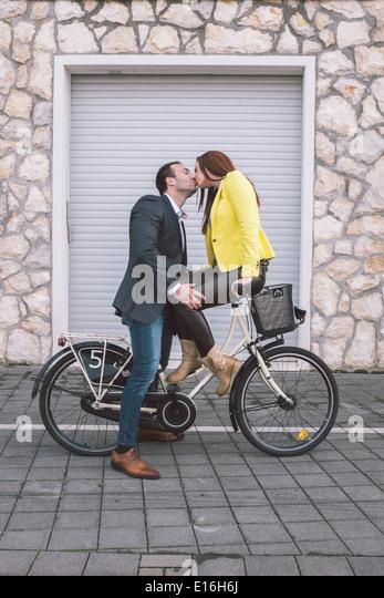 Schönes Paar küssen auf dem Fahrrad Stockbild