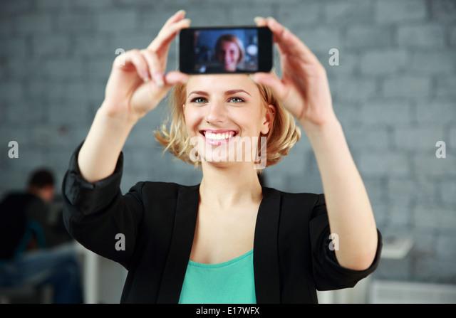 Glückliche Mädchen, ein selbst Foto von ihrem Smartphone im Büro Stockbild