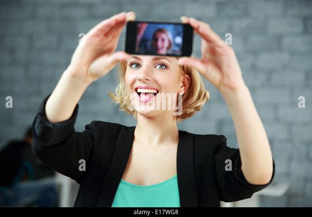 Junge lachende Frau, ein selbst Foto von ihrem Smartphone im Büro Stockbild